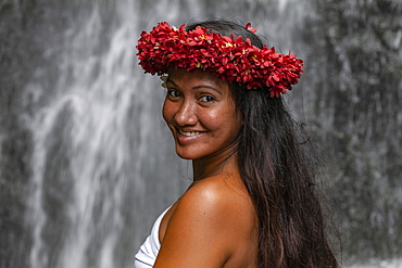 Portrait of a pretty young Tahitian woman with flower headdress in front of waterfall in 'The Water Gardens of Vaipahi', Teva I Uta, Tahiti, Windward Islands, French Polynesia, South Pacific