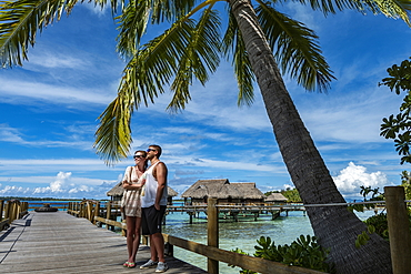 Young couple on boardwalk to overwater bungalows at Sofitel Bora Bora Private Island Resort, Bora Bora, Leeward Islands, French Polynesia, South Pacific