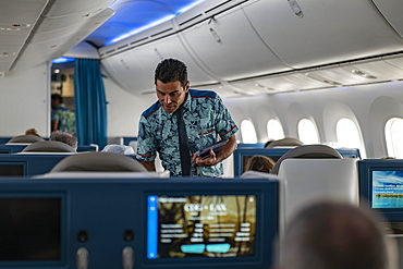 Flight attendant hands menu to passenger in Poerava Business Class aboard Air Tahiti Nui Boeing 787 Dreamliner airplane on the flight from Paris Charles de Gaulle Airport (CDG) in France to Los Angeles International Airport (LAX) in the United States