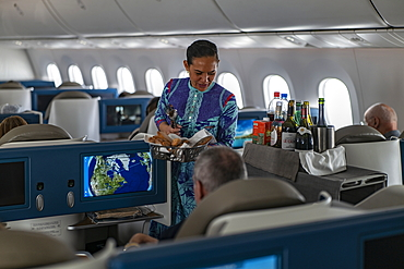 Flight attendant hands bread to passenger in Poerava Business Class aboard Air Tahiti Nui Boeing 787 Dreamliner aircraft on the flight from Paris Charles de Gaulle Airport (CDG) in France to Los Angeles International Airport (LAX) in the United States