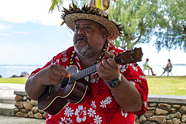 Man playing ukulele guitar and welcoming cruise ship passengers, Moorea, Windward Islands, French Polynesia, South Pacific
