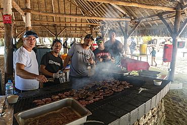 Kitchen crew of the passenger cargo ship Aranui 5 (Aranui Cruises) prepare a beach barbecue for guests on a private Motu islet in the lagoon of Bora Bora, Bora Bora, Leeward Islands, French Polynesia, South Pacific