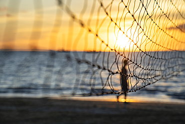 Detail of volleyball net with silhouette of man running on the beach at Pullman Nadi Bay Resort