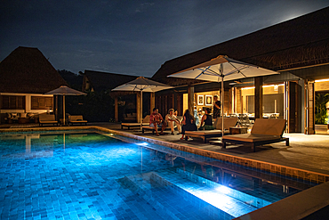 People relaxing by the private swimming pool of a residence villa accommodation at Six Senses Fiji Resort at night, Malolo Island, Mamanuca Group, Fiji Islands, South Pacific