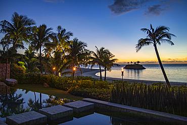 Tiki torches and private swimming pool of a residence villa accommodation at Six Senses Fiji Resort at dusk, Malolo Island, Mamanuca Group, Fiji Islands, South Pacific