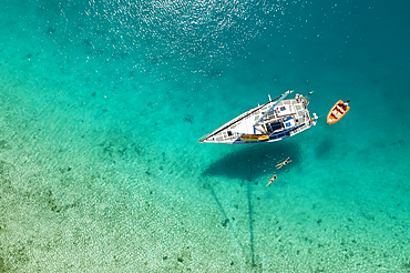 Aerial view of couple swimming from sandbar to their sailboat, near Malolo Island, Mamanuca Group, Fiji Islands, South Pacific