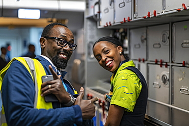 Station manager and flight attendant laugh on board a RwandAir Airbus A330-300 airplane before the flight from Brussels Airport (BRU) in Belgium to Kigali International Airport (KIG) in Rwanda, Brussels, Belgium, Europe