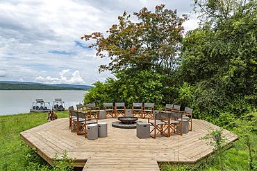 Chairs surround fire pit at the luxury tented resort Magashi Camp (Wilderness Safaris) on the banks of Rwanyakazinga Lake, Akagera National Park, Eastern Province, Rwanda, Africa