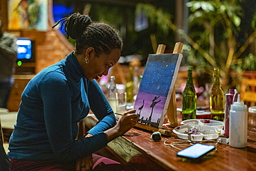 Woman paints picture during painting class event at Heaven Restaurant, Kigali, Kigali Province, Rwanda, Africa