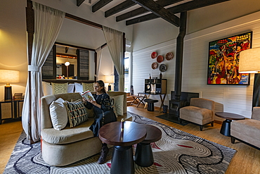 Young woman relaxes in a suite at the luxury resort One