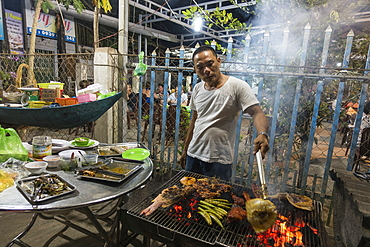 Man grills fresh fish, meat and vegetables at No Name BBQ in Ong Lang Village, Ong Lang, Phu Quoc Island, Kien Giang, Vietnam, Asia