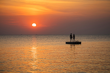 Silhouette of a young couple standing on a bathing platform in front of Ong Lang Beach at sunset, Ong Lang, Phu Quoc Island, Kien Giang, Vietnam, Asia