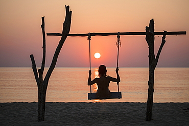 Silhouette of young woman on swing on Ong Lang Beach at sunset, Ong Lang, Phu Quoc Island, Kien Giang, Vietnam, Asia