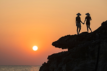 Silhouette of young couple wearing conical hats and looking out to sea from rock ledge next to Dinh Cao Shrine at sunset, Duong Dong, Phu Quoc Island, Kien Giang, Vietnam, Asia