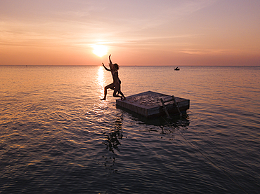 Aerial view silhouette of young couple jumping from a bathing platform at sunset on Ong Lang Beach, Ong Lang, Phu Quoc Island, Kien Giang, Vietnam, Asia