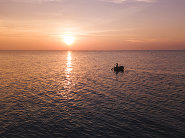 Aerial view silhouette of fisherman in traditional round boat at sunset, Ong Lang, Phu Quoc Island, Kien Giang, Vietnam, Asia