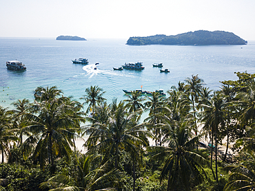 Aerial view of coconut palms near beach with excursion boats, fishing boats and islands in the distance, May Rut Island, near Phu Quoc Island, Kien Giang, Vietnam, Asia