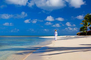 A woman dressed in white, tropical attire walks along a pristine beach. Antiugua, West Indies.