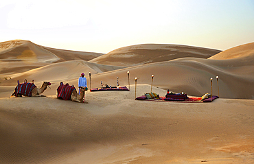 A beautiful desert picninc, set amidst the sanddunes, with a couple of camels and their minder in the foreground. Shot in Saudi Arabia.