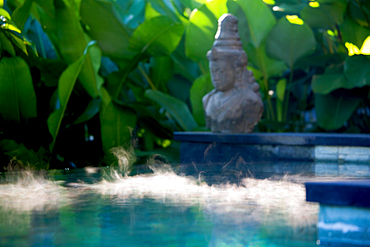 Morning steaam on the surface of a pool with a Hindu statue on the side. Shot in a propical setting. Bali, Indonesia
