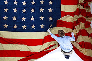 A man folding out a giant American flag. Shot in Texas, USA.