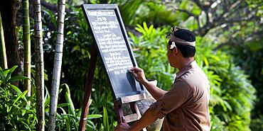 A Balinese waiter writing the daily menu on a blackboard in a tropical setting. Singaraja, Bali.