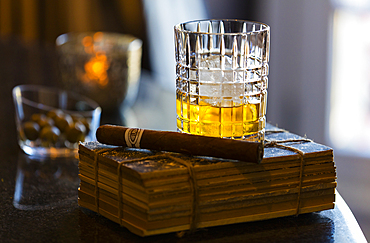 A stillife of a glass of whisky with a cigar set upon an old book. Shot in Algarve, Portugal.