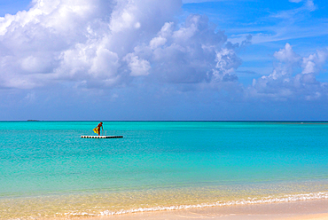 A woman with a bright yellow sarong, standing on a float, off a beach, agains a turqoise sea. Shot in Antigua.