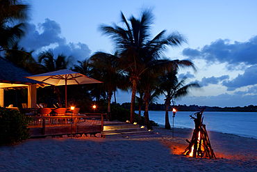 An evening shot of a bonfire set on the beach in front of a beach-terracelit with tiki-lights