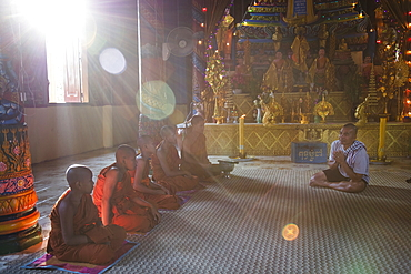 Guide from river cruise ship prays with Buddhist monks in the temple, Preah Prosop, Mekong River, Kandal, Cambodia, Asia