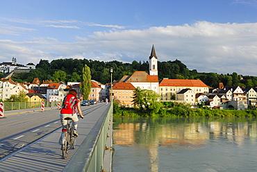 Female cyclist passing bridge over river Inn, Danube Cycle Route Passau Vienna, Passau, Lower Bavaria, Bavaria, Germany