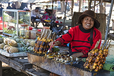 Happy woman with stuffed grilled frog at a street food stall in the market, Oudong (Udong), Kampong Speu, Cambodia, Asia