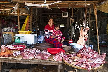 Cheerful woman with daughter at a butcher stall at the street market, Kampong Chhnang, Kampong Chhnang, Cambodia, Asia
