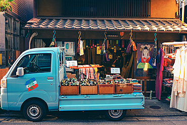 Shop front for textiles in Kyoto with a small delivery truck, Japan