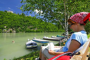 Woman sitting on bench near river Danube while reading, Neuhaus castle, Danube Cycle Route Passau to Vienna, Upper Austria, Austria