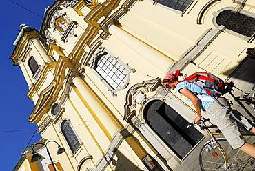 Female cyclist near Ursuline Church, Danube Cycle Route Passau to Vienna, Linz, Upper Austria, Austria