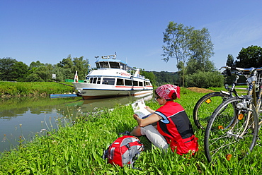 Woman sitting in meadow near river Danube while reading, Ardagger Markt, Lower Austria, Austria