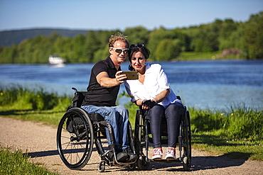 Couple in wheelchairs making selfie photo on the Main, Großwallstadt, Spessart-Mainland, Franconia, Bavaria, Germany, Europe