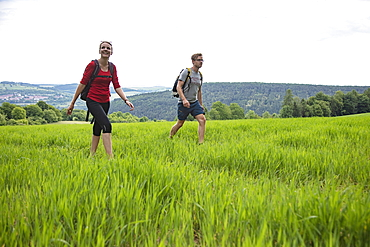 Young woman and young man hiking through field, Tauberbischofsheim, Baden-Wuerttemberg, Germany, Europe