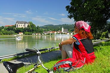 Woman looking over river Danube to Grein, Upper Austria, Austria