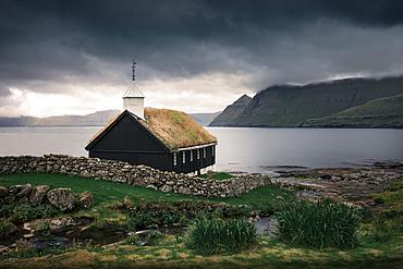 Church of the Funningur Parish on Eysturoy Island under dramatic clouds, Faroe Islands