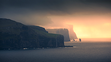 Sunset with clouds on the coast of Eysteroy with steep cliffs and rock formation Risin og Kellingin, Faroe Islands