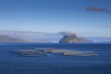 Fish farm off Koltur Island in the sun, Faroe Islands