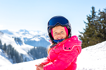Child in the snow in St. Johann in Tirol with Kitzbühel Alps in the background, St. Johann, Tyrol, Austria
