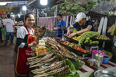 Woman presents a freshly grilled Mekong fish at a sales stall along Sisavangvong Road (the main street), Luang Prabang, Luang Prabang Province, Laos, Asia