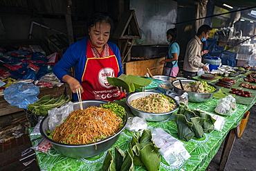 Woman prepares delicacies wrapped in banana leaves for the morning market, Luang Prabang, Luang Prabang Province, Laos, Asia
