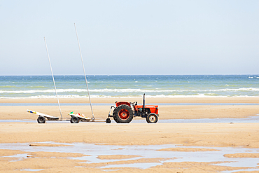 Tractor on the beach with trailer for kite buggies- Omaha Beach, Calvados, France.