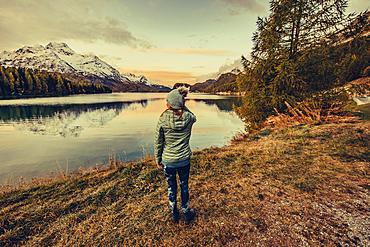 Woman at sunrise on Lake Sils, Engadin, Grisons, Switzerland, Europe