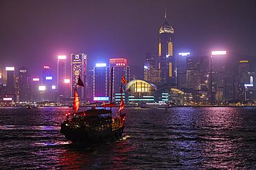 Traditional junk which serves as a tourist sightseeing boat in Victoria Harbor with Hong Kong skyline behind it at night, Hong Kong, Hong Kong, China, Asia