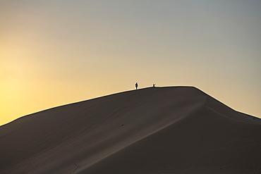 Silhouette of people on sand dune outside Arabian Nights Village desert resort at sunset, Arabian Nights Village, Razeen Area of Al Khatim, Abu Dhabi, United Arab Emirates, Emirates, Middle East